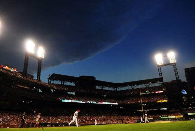 Aug 20, 2014; St. Louis, MO, USA; St. Louis Cardinals first baseman Matt Adams (32) is walked by Cincinnati Reds starting pitcher Johnny Cueto (47) as storm clouds move in during the fifth inning at Busch Stadium. Mandatory Credit: Jeff Curry-USA TODAY Sports