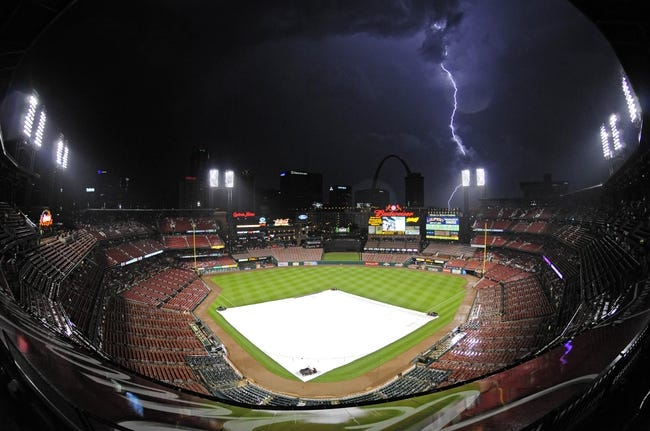 Aug 20, 2014; St. Louis, MO, USA; Lightning strikes after the tarp is put on the field during the eighth inning of a game between the Cincinnati Reds and the St. Louis Cardinals at Busch Stadium. Mandatory Credit: Jeff Curry-USA TODAY Sports