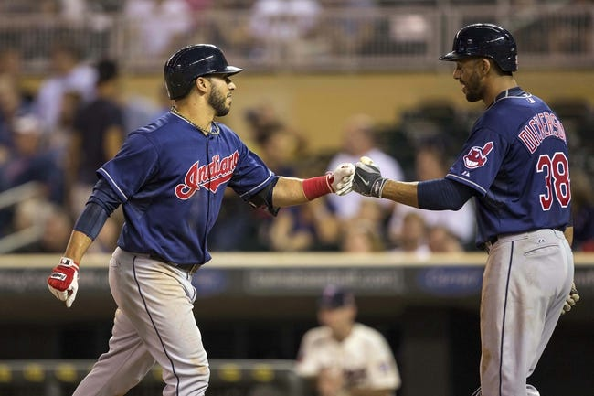 Aug 20, 2014; Minneapolis, MN, USA; Cleveland Indians third baseman Mike Aviles (4) celebrates with Cleveland Indians right fielder Chris Dickerson (38) after hitting a home run in the ninth inning against the Minnesota Twins at Target Field. The Indians won 5-0. Mandatory Credit: Jesse Johnson-USA TODAY Sports
