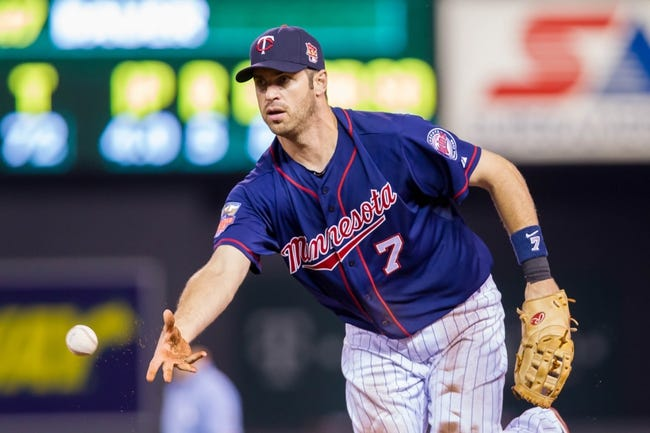 Aug 19, 2014; Minneapolis, MN, USA; Minnesota Twins first baseman Joe Mauer (7) tosses a ball to first against the Cleveland Indians at Target Field. Mandatory Credit: Brad Rempel-USA TODAY Sports