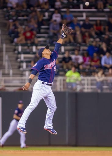 Aug 19, 2014; Minneapolis, MN, USA; Minnesota Twins shortstop Eduardo Escobar (5) jumps for a fly ball against the Cleveland Indians at Target Field. Mandatory Credit: Brad Rempel-USA TODAY Sports