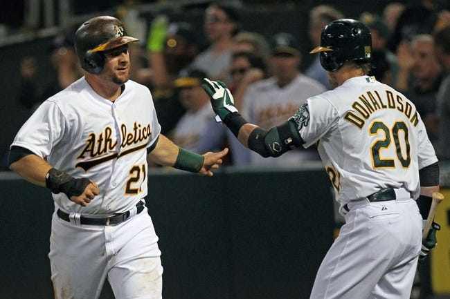 Aug 8, 2014; Oakland, CA, USA; Oakland Athletics first baseman Stephen Vogt (21) is greeted by third baseman Josh Donaldson (20) after scoring one of three runs on a Coco Crisp (4) triple in the fifth inning of their MLB baseball game with the Minnesota Twins at O.co Coliseum. Mandatory Credit: Lance Iversen-USA TODAY Sports