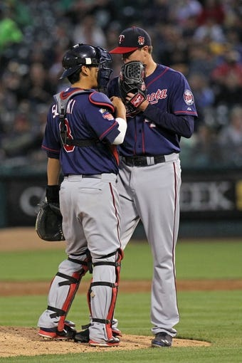 Aug 8, 2014; Oakland, CA, USA; Minnesota Twins catcher Kurt Suzuki (8) talks with his starting pitcher Kyle Gibson (44) after the Oakland Athletics got two runners on base in the fifth inning of their MLB baseball game at O.co Coliseum. Mandatory Credit: Lance Iversen-USA TODAY Sports