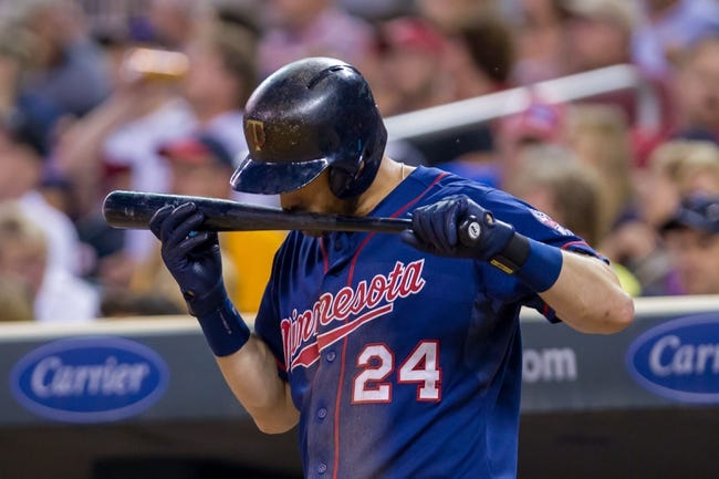 Aug 19, 2014; Minneapolis, MN, USA; Minnesota Twins third baseman Trevor Plouffe (24) smells the pine tar on his bat in the on deck circle against the Cleveland Indians at Target Field. Mandatory Credit: Brad Rempel-USA TODAY Sports