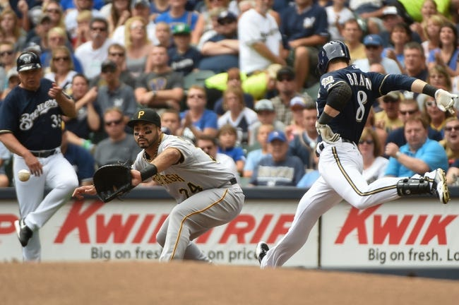 Aug 24, 2014; Milwaukee, WI, USA;   Milwaukee Brewers right fielder Ryan Braun (8) beats out an infield hit as Pittsburgh Pirates first baseman Pedro Alvarez (24) fields the throw in the first inning at Miller Park. Mandatory Credit: Benny Sieu-USA TODAY Sports
