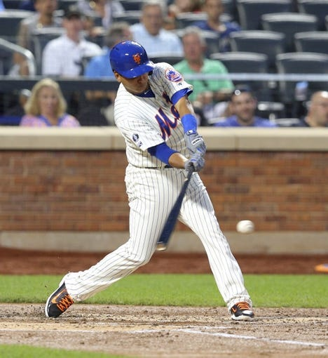 Aug 26, 2014; New York, NY, USA; New York Mets shortstop Ruben Tejada (11) hits an RBI single against the Atlanta Braves during the second inning of a game at Citi Field. Mandatory Credit: Brad Penner-USA TODAY Sports