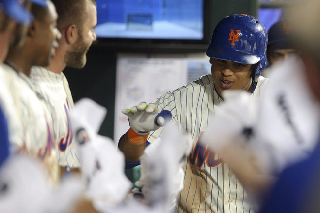 Aug 26, 2014; New York, NY, USA; New York Mets center fielder Juan Lagares (12) is congratulated in the dugout after hitting a two-run home run against the Atlanta Braves during the fourth inning of a game at Citi Field. Mandatory Credit: Brad Penner-USA TODAY Sports