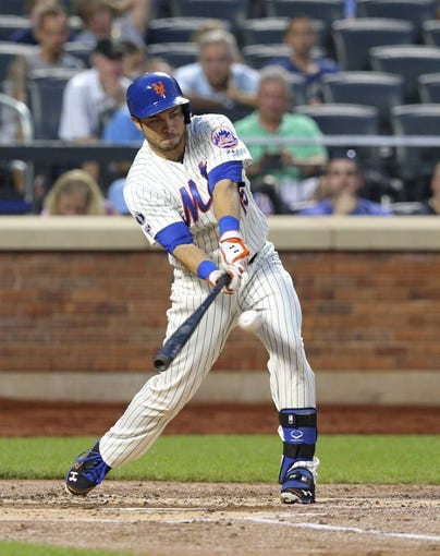 Aug 26, 2014; New York, NY, USA; New York Mets catcher Travis d'Arnaud (15) hits a single against the Atlanta Braves during the second inning of a game at Citi Field. Mandatory Credit: Brad Penner-USA TODAY Sports