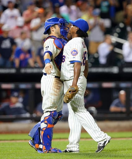 Aug 26, 2014; New York, NY, USA; New York Mets relief pitcher Jenrry Mejia (58) and New York Mets catcher Travis d'Arnaud (15) bump chests after closing the game against the Atlanta Braves at Citi Field. The Mets defeated the Braves 3-2. Mandatory Credit: Brad Penner-USA TODAY Sports