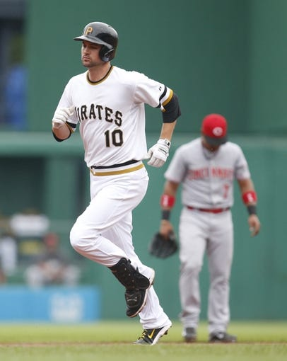 Aug 31, 2014; Pittsburgh, PA, USA; Pittsburgh Pirates shortstop Jordy Mercer (10) rounds the bases after hitting a solo home run as Cincinnati Reds shortstop Ramon Santiago (7) reacts during the second inning at PNC Park. Mandatory Credit: Charles LeClaire-USA TODAY Sports