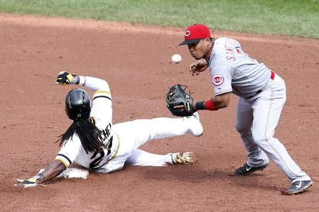 Aug 31, 2014; Pittsburgh, PA, USA; Pittsburgh Pirates center fielder Andrew McCutchen (22) slides into second base causing Cincinnati Reds shortstop Ramon Santiago (7) to lose the ball on a double play attempt during the sixth inning at PNC Park. The Reds won 3-2. Mandatory Credit: Charles LeClaire-USA TODAY Sports
