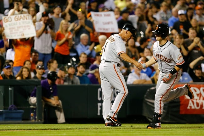 Sep 2, 2014; Denver, CO, USA; San Francisco Giants first baseman Buster Posey (28) celebrates with third base coach Tim Flannery (1) after hitting a home run in the sixth inning against the Colorado Rockies at Coors Field. Mandatory Credit: Isaiah J. Downing-USA TODAY Sports