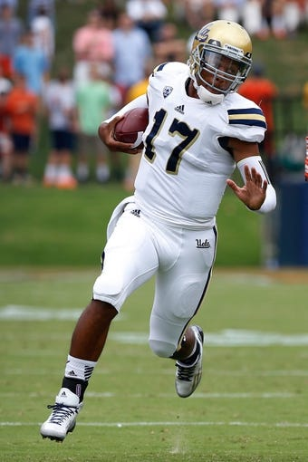 Aug 30, 2014; Charlottesville, VA, USA; UCLA Bruins quarterback Brett Hundley (17) runs with the ball against the Virginia Cavaliers at Scott Stadium. Mandatory Credit: Geoff Burke-USA TODAY Sports