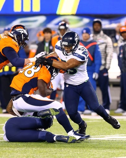 Feb 2, 2014; East Rutherford, NJ, USA; Seattle Seahawks linebacker Malcolm Smith (53) tackles Denver Broncos running back Montee Ball (28) in Super Bowl XLVIII at MetLife Stadium.  Mandatory Credit: Mark J. Rebilas-USA TODAY Sports