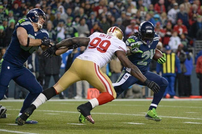 Jan 19, 2014; Seattle, WA, USA; Seattle Seahawks running back Marshawn Lynch (24) runs with the football against San Francisco 49ers outside linebacker Aldon Smith (99) during the second half of the 2013 NFC Championship football game at CenturyLink Field. The Seahawks defeated the 49ers 23-17. Mandatory Credit: Kyle Terada-USA TODAY Sports