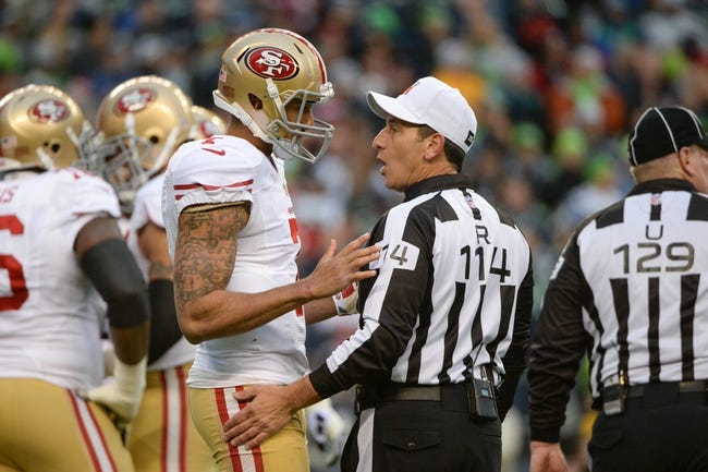 Jan 19, 2014; Seattle, WA, USA; San Francisco 49ers quarterback Colin Kaepernick (7) talks to NFL referee Gene Steratore (114) during the first half of the 2013 NFC Championship football game against the Seattle Seahawks at CenturyLink Field. The Seahawks defeated the 49ers 23-17. Mandatory Credit: Kyle Terada-USA TODAY Sports