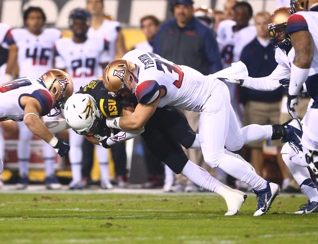 Nov 30, 2013; Tempe, AZ, USA; Arizona State Sun Devils running back D.J. Foster (8) is tackled by Arizona Wildcats linebacker Jake Fischer (33) in the 87th annual Territorial Cup at Sun Devil Stadium. Mandatory Credit: Mark J. Rebilas-USA TODAY Sports
