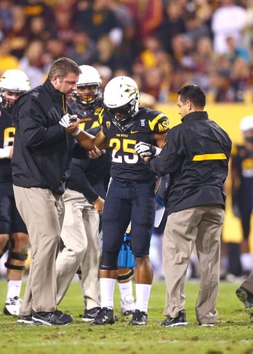 Nov 30, 2013; Tempe, AZ, USA; Arizona State Sun Devils running back Deantre Lewis (25) is helped up by trainers after suffering an injury against the Arizona Wildcats in the 87th annual Territorial Cup at Sun Devil Stadium. Mandatory Credit: Mark J. Rebilas-USA TODAY Sports