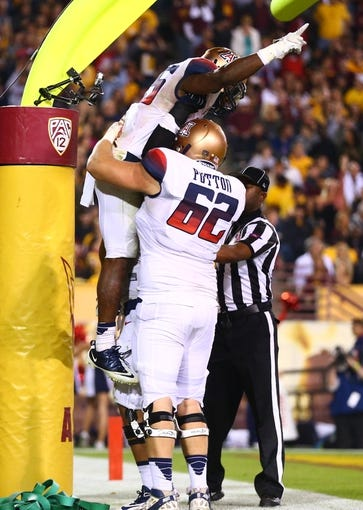 Nov 30, 2013; Tempe, AZ, USA; Arizona Wildcats running back Ka'Deem Carey (25) celebrates a touchdown with offensive lineman Chris Putton (62) in the second half against the Arizona State Sun Devils in the 87th annual Territorial Cup at Sun Devil Stadium. Arizona State defeated Arizona 58-21. Mandatory Credit: Mark J. Rebilas-USA TODAY Sports