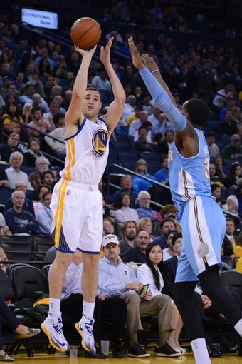 April 10, 2014; Oakland, CA, USA; Golden State Warriors guard Klay Thompson (11) shoots the ball against Denver Nuggets forward Quincy Miller (30) during the third quarter at Oracle Arena. The Nuggets defeated the Warriors 100-99. Mandatory Credit: Kyle Terada-USA TODAY Sports