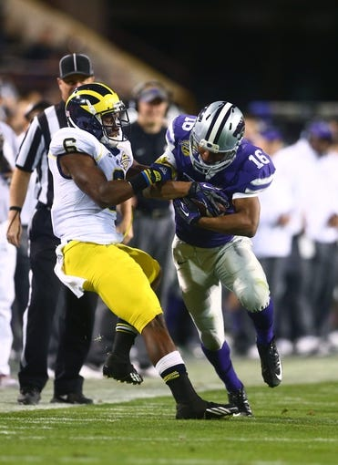 Dec 28, 2013; Tempe, AZ, USA; Kansas State Wildcats wide receiver Tyler Lockett (16) is tackled by Michigan Wolverines defensive back Raymon Taylor (6) during the Buffalo Wild Wings Bowl at Sun Devil Stadium. Mandatory Credit: Mark J. Rebilas-USA TODAY Sports