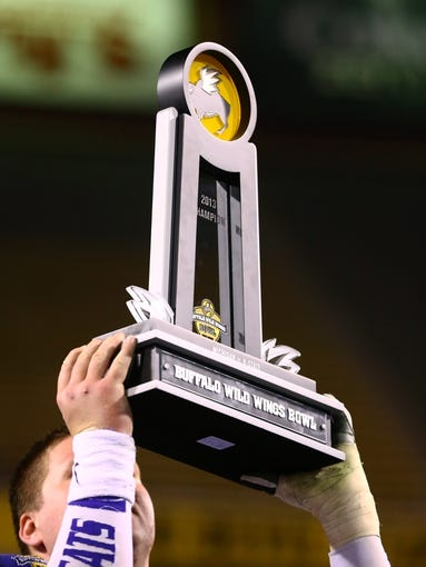 Dec 28, 2013; Tempe, AZ, USA; Detailed view of the trophy as a Kansas State Wildcats celebrates after defeating the Michigan Wolverines during the Buffalo Wild Wings Bowl at Sun Devil Stadium. Kansas State defeated Michigan 31-14. Mandatory Credit: Mark J. Rebilas-USA TODAY Sports