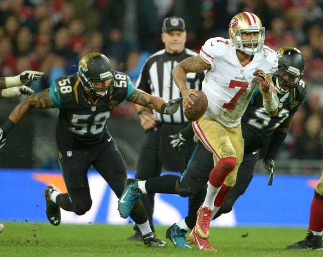 Oct 27, 2013; London, United Kingdom; San Francisco 49ers quarterback Colin Kaepernick (7) is pursued by Jacksonville Jaguars defensive end Jason Babiin (58) and defensive tackle Brandon Deaderick (92) in the NFL International Series game at Wembley Stadium. The 49ers defeated the Jaguars 42-10. Mandatory Credit: Kirby Lee-USA TODAY Sports