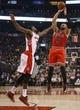 Apr 12, 2013; Toronto, Ontario, CAN; Chicago Bulls forward Carlos Boozer (5) shoots as Toronto Raptors center-forward Amir Johnson (15) defends at the Air Canada Centre. Toronto defeated Chicago 97-88. Mandatory Credit: John E. Sokolowski-USA TODAY Sports