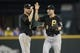 Jun 26, 2013; Seattle, WA, USA; Pittsburgh Pirates shortstop Jordy Mercer (10) celebrates the final out against the Seattle Mariners with second barman Neil Walker (18) at Safeco Field. Pittsburgh defeated Seattle, 4-2. Mandatory Credit: Joe Nicholson-USA TODAY Sports