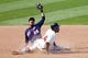 Aug 25, 2013; Cleveland, OH, USA; Minnesota Twins shortstop Pedro Florimon (25) holds up the ball as Cleveland Indians center fielder Michael Bourn (24) slides safely into the base with a double in the eighth inning at Progressive Field. Mandatory Credit: David Richard-USA TODAY Sports