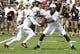 Aug 31, 2013; Cincinnati, OH, USA; Cincinnati Bearcats quarterback Munchie Legaux (4) hands off to running back Ralph Abernathy (1)during the first quarter at Nippert Stadium. Mandatory Credit: David Kohl-USA TODAY Sports