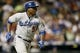 Sep 4, 2013; Denver, CO, USA; Los Angeles Dodgers third baseman Juan Uribe (5) runs to first base on a RBI double during the eighth inning against the Colorado Rockies at Coors Field. The Rockies won 7-5.  Mandatory Credit: Chris Humphreys-USA TODAY Sports