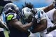 Sep 8, 2013; Charlotte, NC, USA; Carolina Panthers running back DeAngelo Williams (34) is tackled by Seattle Seahawks defensive tackle Tony McDaniel (99) in the first quarter. The Seahawks defeated the Panthers 12-7 at Bank of America Stadium. Mandatory Credit: Bob Donnan-USA TODAY Sports