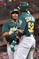 Sep 10, 2013; Minneapolis, MN, USA; Oakland Athletics second baseman Alberto Callaspo (18) is congratulated by outfielder Yoenis Cespedes (52) after hitting a home run during the fifth inning against the Minnesota Twins at Target Field. Mandatory Credit: Brace Hemmelgarn-USA TODAY Sports