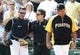 Sep 19, 2013; Pittsburgh, PA, USA; Pittsburgh Pirates catcher Tony Sanchez (left) is checked by a team trainer and manager Clint Hurdle (13) after Sanchez tumbled into the San Diego Padres dugout to record an out during the eighth inning at PNC Park. The Pittsburgh Pirates won 10-1. Mandatory Credit: Charles LeClaire-USA TODAY Sports