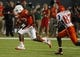 Sep 21, 2013; Miami Gardens, FL, USA;  Miami Hurricanes defensive back A.J. Highsmith (30) intercepts as Savannah State Tigers wide receiver Jeremmia Harris chases in the second quarter at Sun Life Stadium. Mandatory Credit: Robert Mayer-USA TODAY Sports