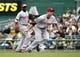 Sep 22, 2013; Pittsburgh, PA, USA; Cincinnati Reds first baseman Joey Votto (front) tosses to first base to retire a Pittsburgh Pirates batter during the fourth inning at PNC Park.  The Reds won 11-3. Mandatory Credit: Charles LeClaire-USA TODAY Sports