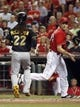 Sep 27, 2013; Cincinnati, OH, USA; Cincinnati Reds starting pitcher Homer Bailey (34) runs by Pittsburgh Pirates center fielder Andrew McCutchen (22) as he scores at home after a Marlon Byrd (not pictured) two-RBI single in the third inning at Great American Ball Park. Mandatory Credit: David Kohl-USA TODAY Sports