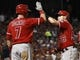 Sep 27, 2013; Arlington, TX, USA; Los Angeles Angels right fielder Kole Calhoun (56) is congratulated by third baseman Andrew Romine (7) after scoring against the Texas Rangers during the fifth inning at Rangers Ballpark. Mandatory Credit: Jim Cowsert-USA TODAY Sports