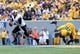 Sep 28, 2013; Morgantown, WV, USA; Oklahoma State Cowboys quarterback J.W. Walsh (4) rolls out to pass against West Virginia Mountaineers defensive lineman Darren Arndt (89) during the first half at Milan Puskar Stadium. Mandatory Credit: Peter Casey-USA TODAY Sports