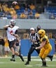 Sep 28, 2013; Morgantown, WV, USA; Oklahoma State Cowboys quarterback J.W. Walsh (4) throws a pass against West Virginia Mountaineers linebacker Jared Barber (33) during the first half at Milan Puskar Stadium. Mandatory Credit: Peter Casey-USA TODAY Sports