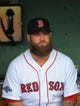 Oct 5, 2013; Boston, MA, USA; Boston Red Sox first baseman Mike Napoli (12) sits in the dugout prior to game two of the American League divisional series playoff baseball game against the Tampa Bay Rays at Fenway Park. Mandatory Credit: Bob DeChiara-USA TODAY Sports