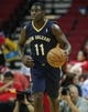 Oct 5, 2013; Houston, TX, USA; New Orleans Pelicans point guard Jrue Holiday (11) brings the ball up the court against the Houston Rockets at Toyota Center. Mandatory Credit: Troy Taormina-USA TODAY Sports