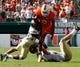 Oct 26, 2013; Miami Gardens, FL, USA; Miami Hurricanes running back Duke Johnson (8) leaps over Wake Forest Demon Deacons linebacker Mike Olson (bottom) as safety Ryan Janvion (22) attempts a tackle in in the second half at Sun Life Stadium. Miami won 24-21. Mandatory Credit: Robert Mayer-USA TODAY Sports