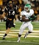 Oct 26, 2013; Hattiesburg, MS, USA; North Texas Mean Green wide receiver Carlos Harris (9) runs away from Southern Miss Golden Eagles linebacker Terrick Wright (14) in the second quarter of their game at M.M. Roberts Stadium. Mandatory Credit: Chuck Cook-USA TODAY Sports
