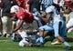 Nov 2, 2013; Raleigh, NC, USA; North Carolina State Wolfpack quarterback Brandon Mitchell (8) falls over North Carolina Tar Heels cornerback Jabari Price (4) during a first half run at Carter Finley Stadium. Mandatory Credit: Rob Kinnan-USA TODAY Sports