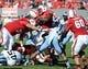 Nov 2, 2013; Raleigh, NC, USA; North Carolina State Wolfpack quarterback Brandon Mitchell (8) is tackled by North Carolina Tar Heels linebacker Travis Hughes (9) as he runs during the first half at Carter Finley Stadium. Mandatory Credit: Rob Kinnan-USA TODAY Sports