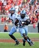 Nov 2, 2013; Raleigh, NC, USA; North Carolina Tar Heels quarterback Bryn Renner (2) hands off to tailback A.J. Blue (15) during the second half against the North Carolina State Wolfpack at Carter Finley Stadium.  North Carolina beat North Carolina State 27-19.  Mandatory Credit: Rob Kinnan-USA TODAY Sports