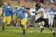 Nov 2, 2013; Pasadena, CA, USA; UCLA Bruins running back Damien Thigpen (25) is pursued by Colorado Buffaloes safety Jered Bell (21) at Rose Bowl. UCLA defeated Colorado 45-23. Mandatory Credit: Kirby Lee-USA TODAY Sports