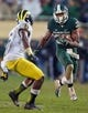 Nov 2, 2013; East Lansing, MI, USA; Michigan State Spartans running back Jeremy Langford (33) run the ball against Michigan Wolverines defensive back Raymon Taylor (6) during the 2nd half of a game against the Michigan Wolverines at Spartan Stadium. MSU won 29-6. Mandatory Credit: Mike Carter-USA TODAY Sports